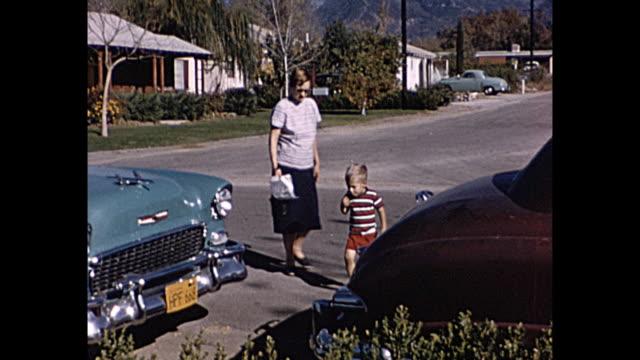 vídeos de stock e filmes b-roll de 1958 home movie young boy running around front yard while, women chatting, classic cars - fora de moda estilo