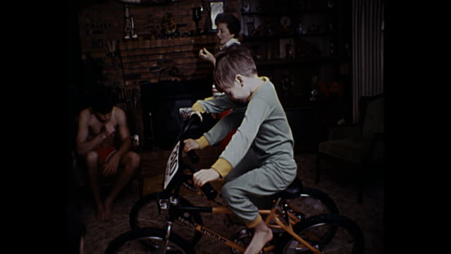 1980 home movie - young boys opening christmas presents by christmas tree - christmas gift stock videos & royalty-free footage
