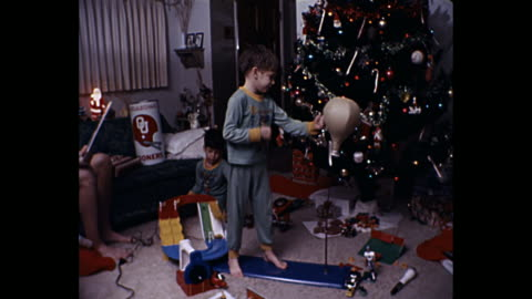 vidéos et rushes de 1980 home movie - young boys playing with new toys by christmas tree - film d'amateur
