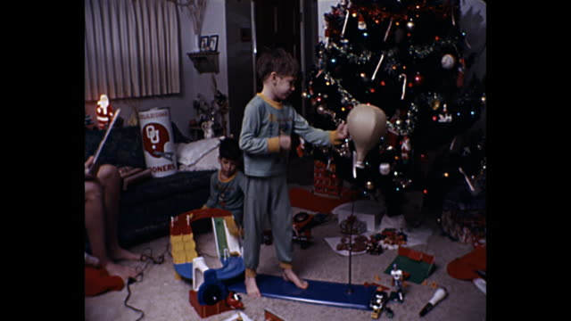 1980 home movie - young boys playing with new toys by christmas tree - 1980 stock videos & royalty-free footage