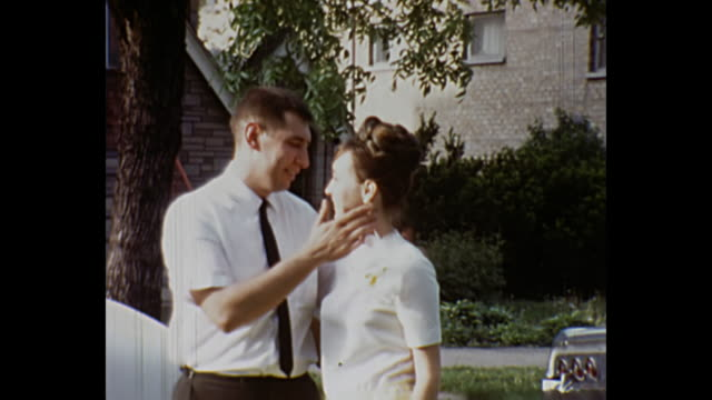 1966 home movie - young couple hug and kiss in their front yard - 1966 stock videos and b-roll footage