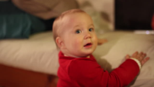 Home movies of a baby in a family wearing a red sweater.