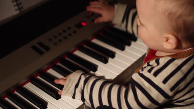 home movies of a baby in a family wearing a striped sweater to match a piano. - abbigliamento da neonato video stock e b–roll