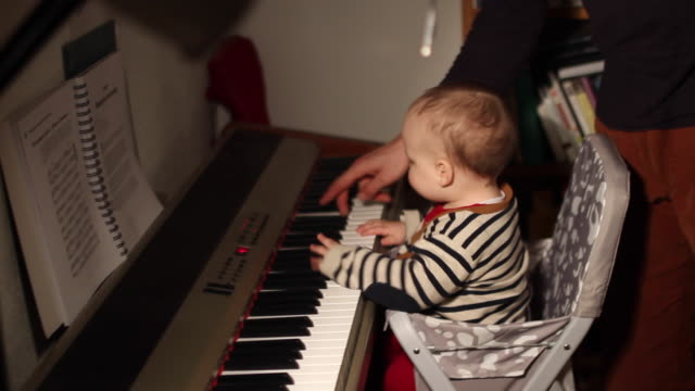 home movies of a baby in a family wearing a striped sweater to match a piano. - piano stock videos & royalty-free footage