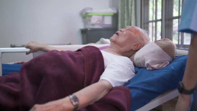 vidéos et rushes de infirmière à la maison inclining lit réglable électrique pour le patient masculin aîné - visite à domicile