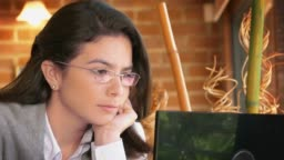 Home Office. Close-up dolly shot of a freelance Hispanic young woman reading on the laptop screen at home
