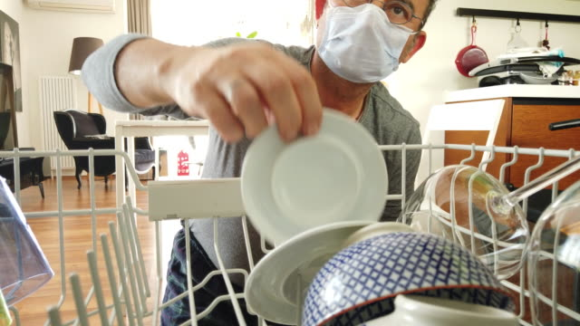 vídeos de stock e filmes b-roll de home quarantine for coronavirus covid-19 epidemic. middle age man wearing a protective face mask is to empty the dishwasher at home - prato vazio