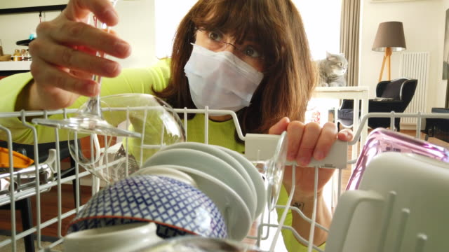 home quarantine for coronavirus covid-19 epidemic. middle age woman wearing a protective face mask is to empty the dishwasher at home - chores stock videos & royalty-free footage