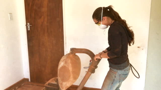 Home Renovations Woman sanding old parquet floors with sanding machine