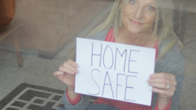 home safe during airborne illness crisis mature female shelter at home during quarantine handheld signs 4k video series - holding stock videos & royalty-free footage