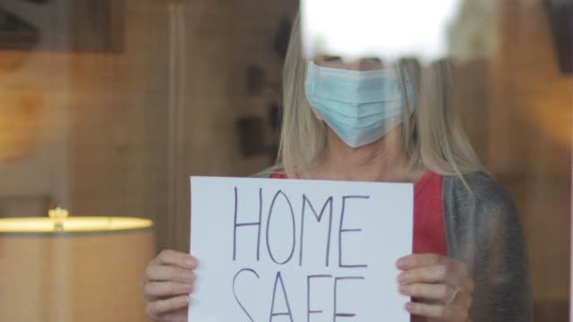 home safe during airborne illness crisis mature female shelter at home during quarantine handheld signs 4k video series - illness prevention stock videos & royalty-free footage