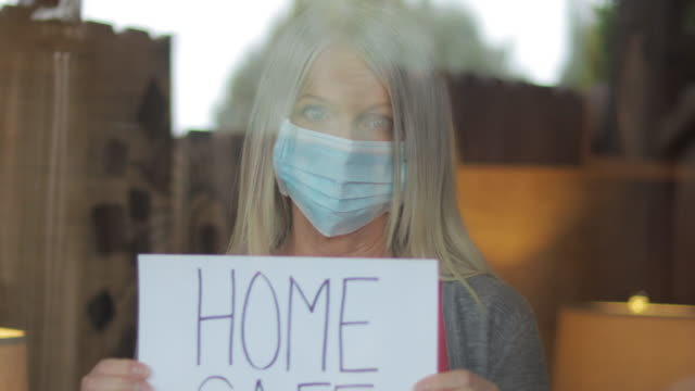 home safe during airborne illness crisis mature female shelter at home during quarantine handheld signs 4k video series - prevenzione delle malattie video stock e b–roll