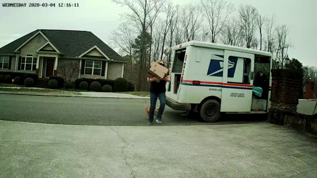 home security camera point of view of a usps mailwoman delivering while feeding a dog amid the 2020 global coronavirus pandemic. - moving after stock videos & royalty-free footage