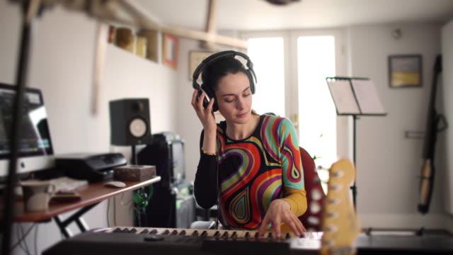 vidéos et rushes de femme de pianiste de studio à la maison - singer