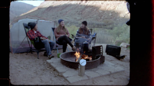 Home video film footage of friends on camping trip sitting around fire pit and talking.