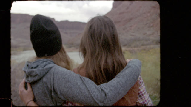 vídeos de stock e filmes b-roll de home video film footage of two young women on camping trip hugging by colorado river and turning to smile at camera. - território selvagem