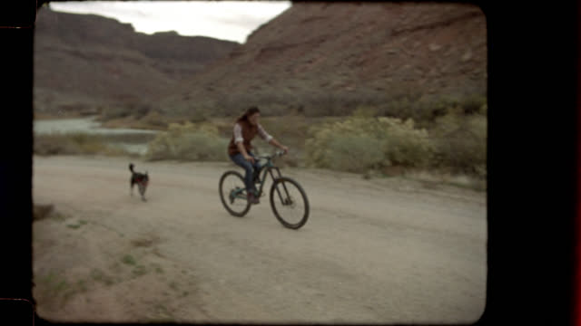 home video film footage of woman biking on trail by colorado river with dog following behind and wagging tail. - pet owner stock videos & royalty-free footage