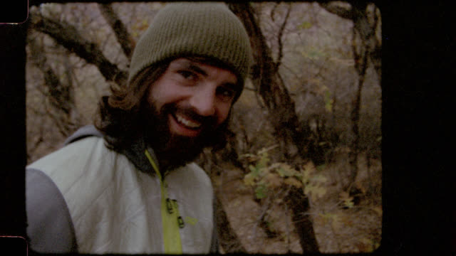 Home video film footage of young man smiling at camera as he prepares food on camping trip.