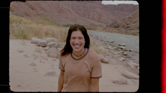 vídeos de stock e filmes b-roll de home video film footage of young woman looking at the camera and smiling on camping trip by the colorado river. - território selvagem