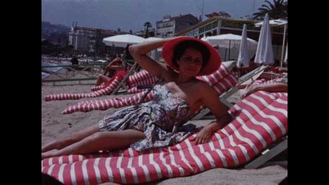 vidéos et rushes de home video footage of a beach in cannes next to carlton pier with people sun bathing and playing volleyball circa 1958 - bain de soleil