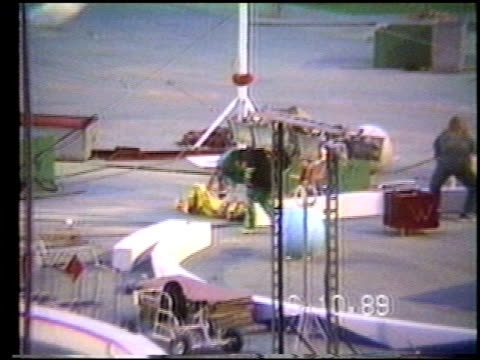 / home video of man doing trapeze circus trick at the shriner's circus where he walks on top of a spinning wheel / he tries to get down but slips and... - braccio umano video stock e b–roll