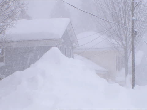 vidéos et rushes de home w/ huge tall snowdrift mound in front of small town home, house by road. blizzard, whiteout conditions, heavy snowing, no people. - neige fraîche