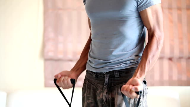 home workout: resistance bands bicep curls exercising living room - home workout stock videos & royalty-free footage