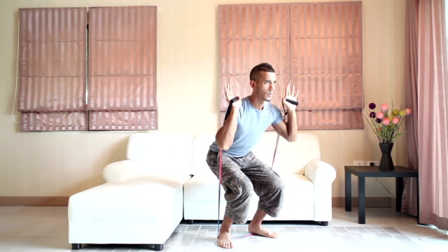 home workout: resistance bands squats exercising living room - crouching stock videos & royalty-free footage