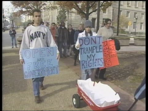 washington dc protestors along to justice department wheeling cart with petitions protesting at erosion of privacy laws by government - department of justice stock videos & royalty-free footage