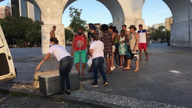 vídeos de stock, filmes e b-roll de homeless and unemployed people receive food and water from volunteers of the 'covid sem fome' on april 22, 2020 in rio de janeiro, brazil. 'covid sem... - desemprego