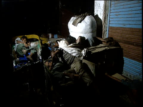 Homeless boys sleeping in back streets of city awake and set off for work bearing sacks for collecting rubbish New Delhi
