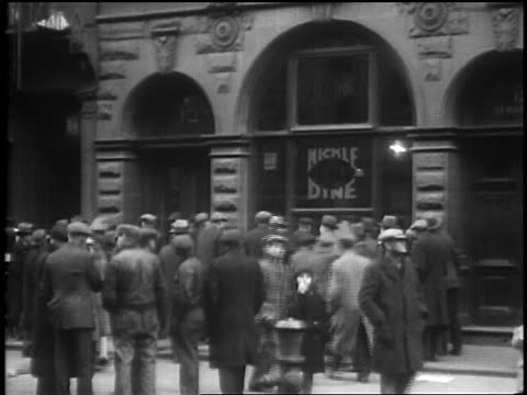 vídeos de stock, filmes e b-roll de homeless crowd around nickel dine waiting to be fed / depression / newsreel - 1920 1929