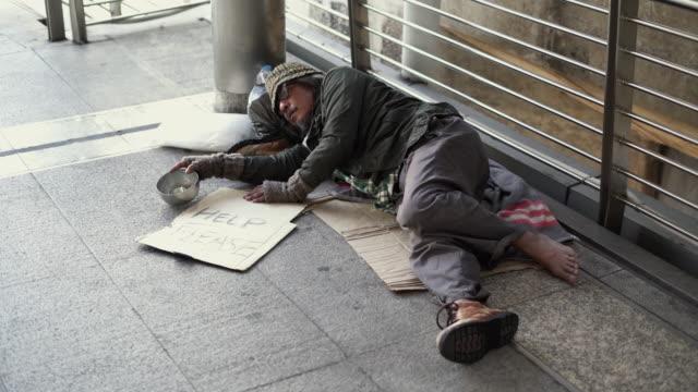 ホームレス、歩道で托鉢を保持しています。 - アキレス腱点の映像素材/bロール