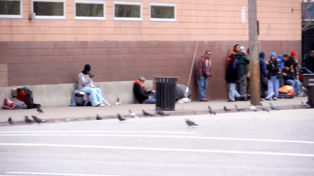 Homeless individuals gather outside of St Vincent de Paul Soup Kitchen in downtown Salt Lake City UT