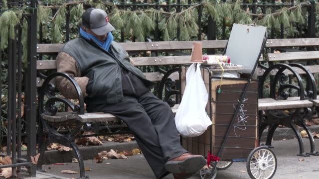 homeless man, bundled up from the cold weather rests on a park bench in the flatiron district of new york city. - ホームレス点の映像素材/bロール