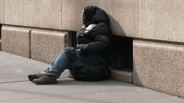 A homeless man bundled up from the cold weather sits on the sidewalk in front of high end stores on 5th Avenue New York City