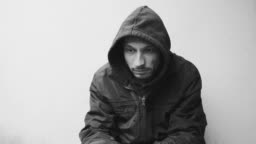 Homeless man drug and alcohol addict sitting alone and depressed on the street in winter clothes feeling anxious cold and lonely, social documentary concept dramatic black and white dark hard contrast