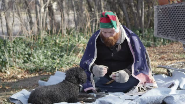 Homeless man eating bread and feeding dog