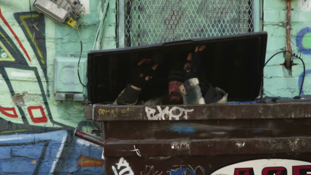 ms homeless man exiting garbage container, salt lake city, utah, usa - container stock-videos und b-roll-filmmaterial