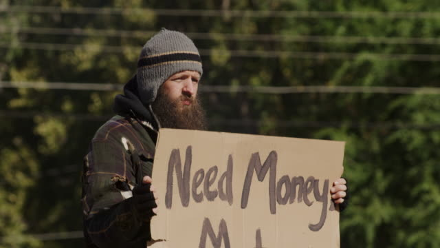 homeless man holding a sign for money - krise stock-videos und b-roll-filmmaterial