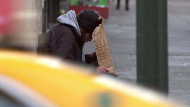 homeless man holds a cardboard sign. he rests his head. - povertà video stock e b–roll