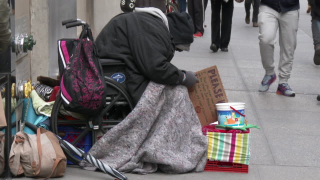 a homeless man holds a please help sign as he sits on the sidewalk bundled up from the cold weather on 5th avenue new york city - homelessness stock videos & royalty-free footage