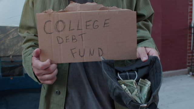"cu homeless man holds ""college debt fund"" sign outside his sidewalk tent - housing difficulties stock videos & royalty-free footage"