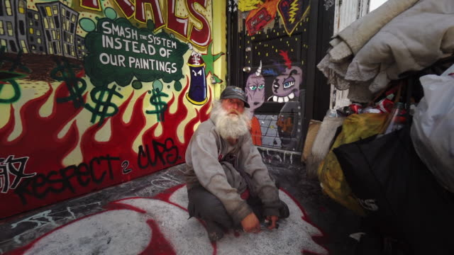 homeless man near street art (graffiti) in clarion alley, san francisco, usa - homelessness stock videos & royalty-free footage