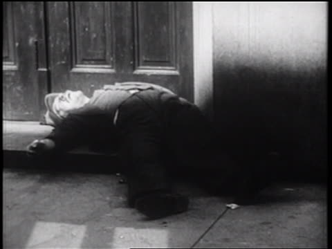 B/W 1939 homeless man passed out in doorway on city sidewalk / NYC / documentary
