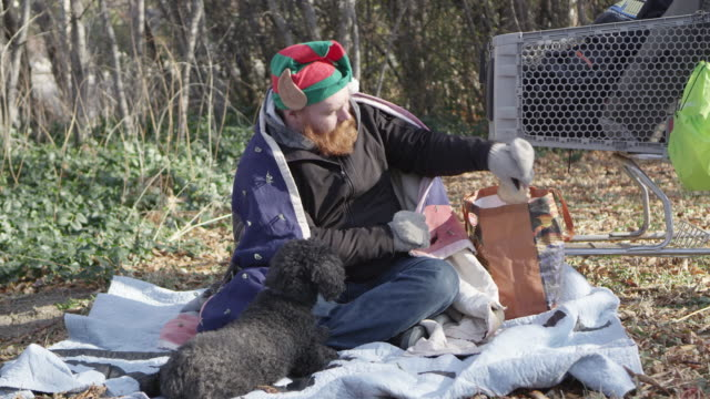 Homeless man pulling bread out of bag to share with dog
