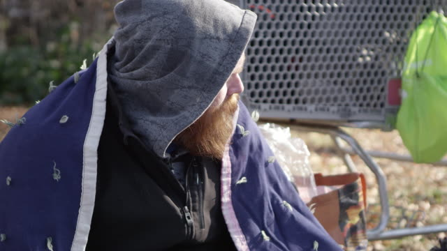 Homeless man pulling hood down to cover faces to keep warm