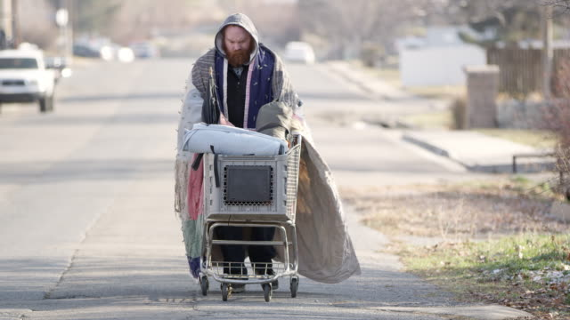 Homeless man pushing shopping cart down the street