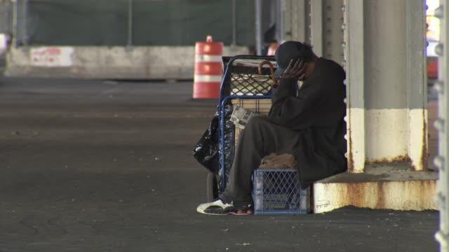 vidéos et rushes de ws homeless man reading paper while sitting at bottom roadway beam / new york city, new york, usa - mal logés