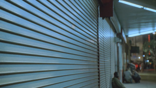 a homeless man sits on a sidewalk and leans against the shutters of a shop closed for the night. - shutter stock videos and b-roll footage